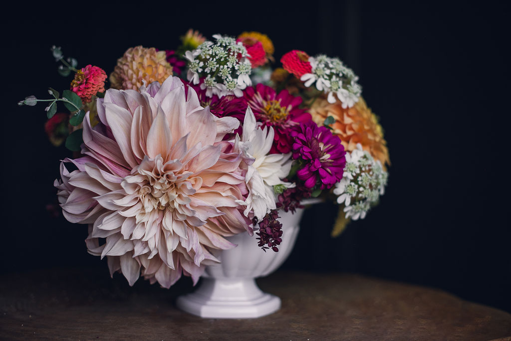 autumn bouquet in a white bowl featuring a large pink dahlia and zinnias