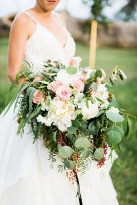 bride holding a large garden style white and pink bouquet