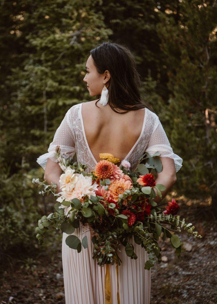 bride with an open back dress holding an autumn garden style elopement bouquet behind her back