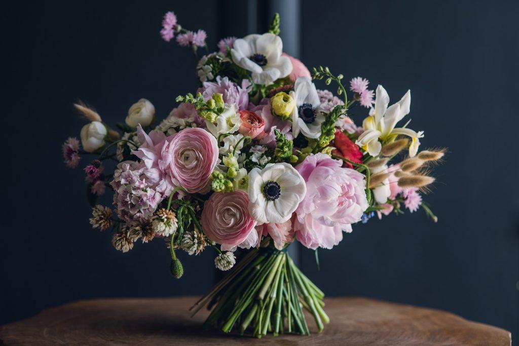 large spring bouquet full of pink ranunculus, anemones, iris, cherry blossom