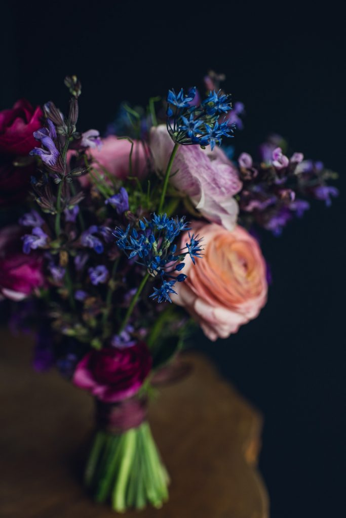 small summer bouquet with blue allium, coral and lavender ranunculus, and purple larkspur