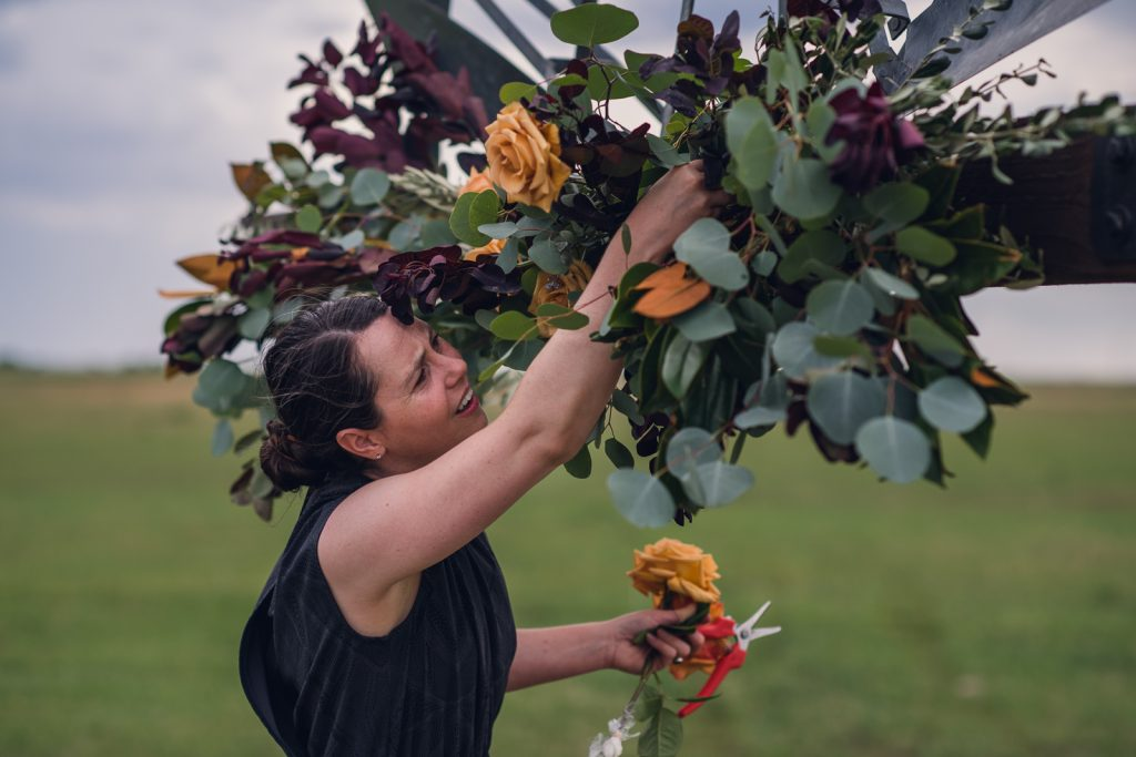 woman in a black dress creating a flower swag for a wedding