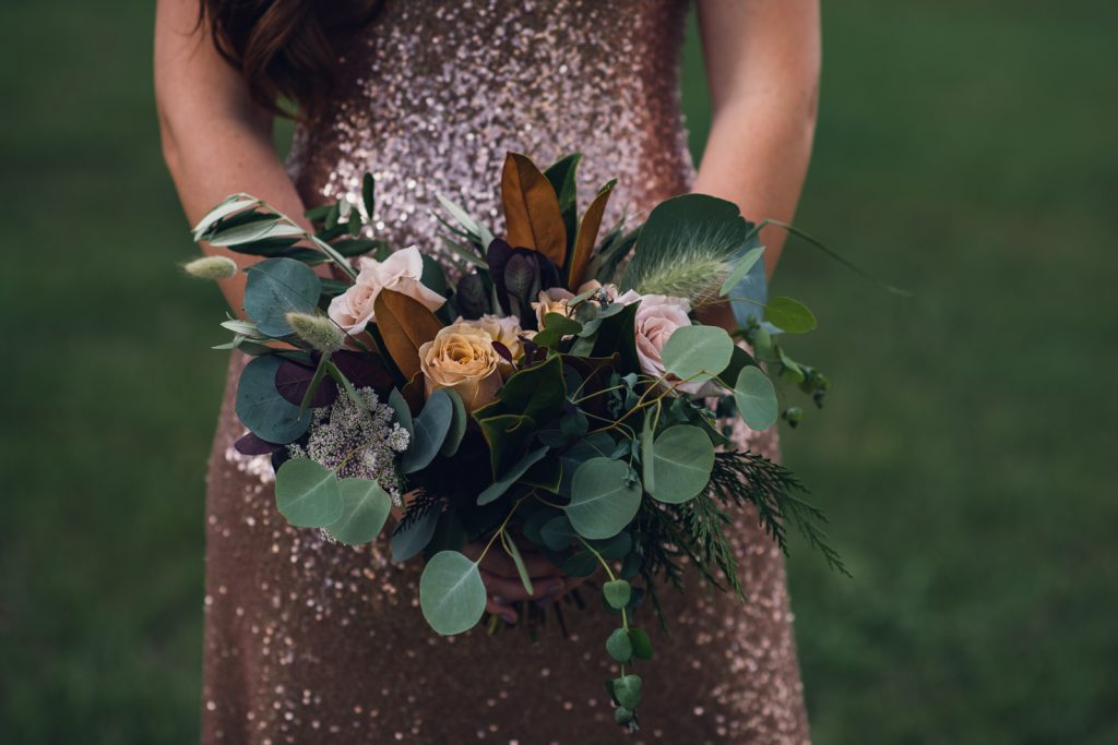 bridesmaid in a sequin rose gold dress holding a bouquet of roses and eucalyptus
