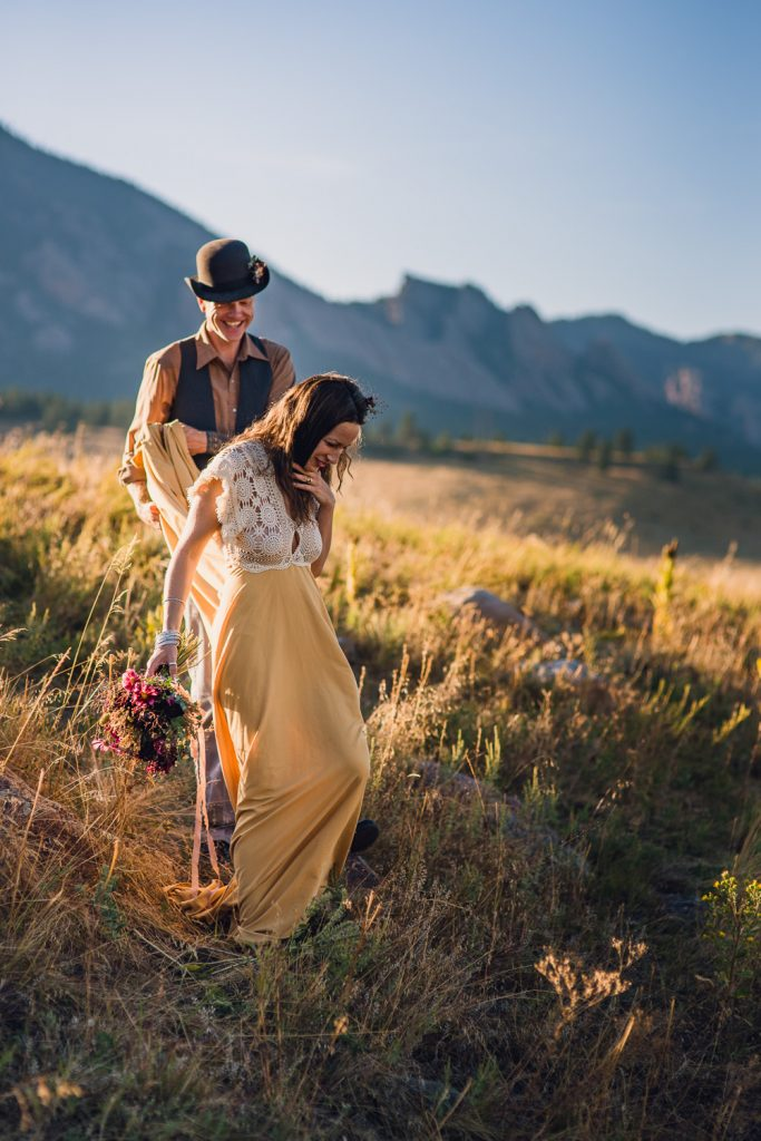 groom helping bride with the train on her yellow dress during colorado mountain elopement
