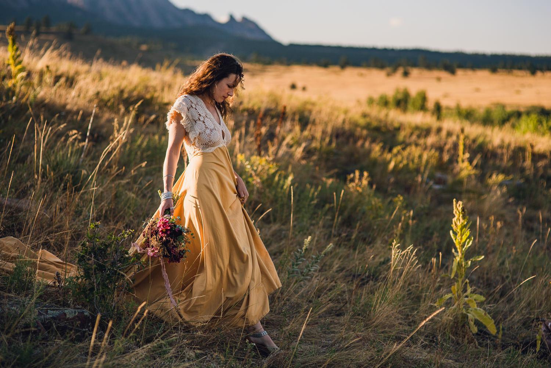 bride in a yellow dress holding elopement bouquet walking through golden grass in boulder colorado