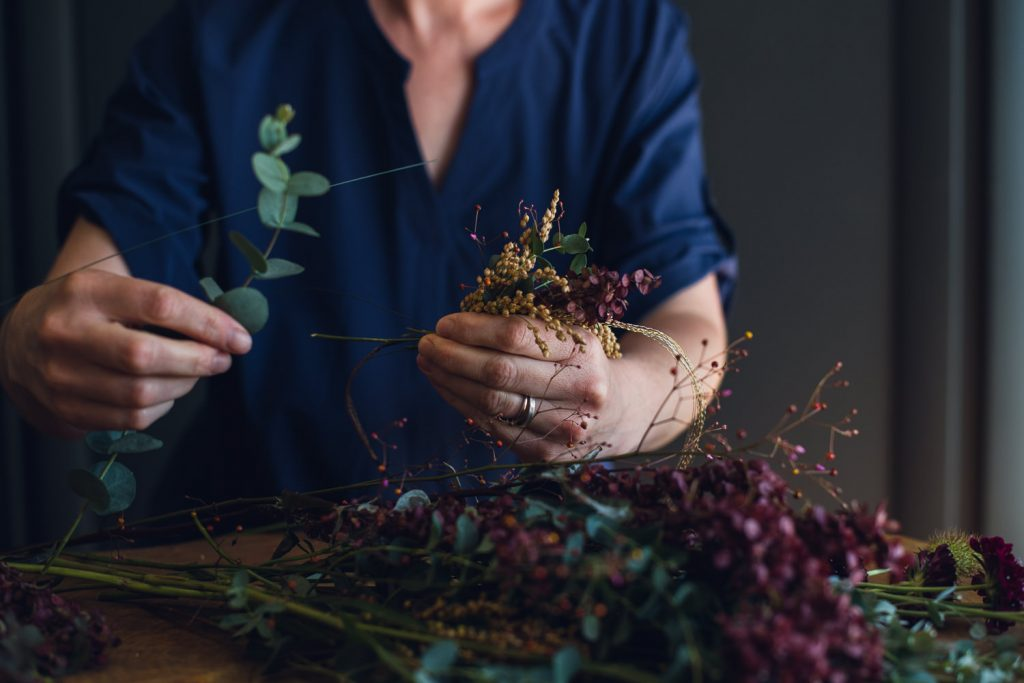 florist holding small flower pieces to create a flower crown