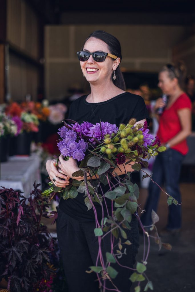 woman in sunglasses holding a large bunch of flowers to create a wedding bouquet