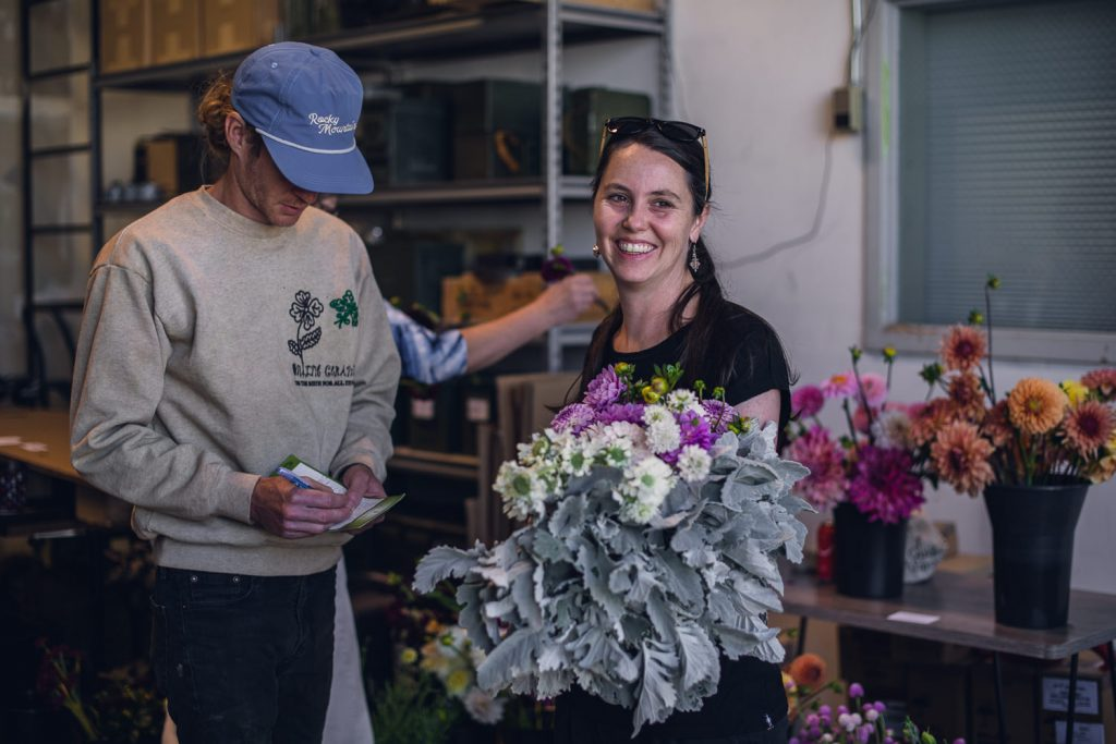 florist holding a bunch of flowers in a warehouse
