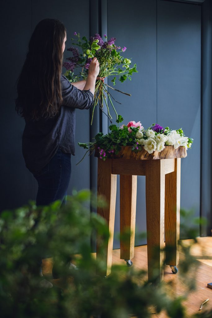 woman in a studio creating floral bouquets