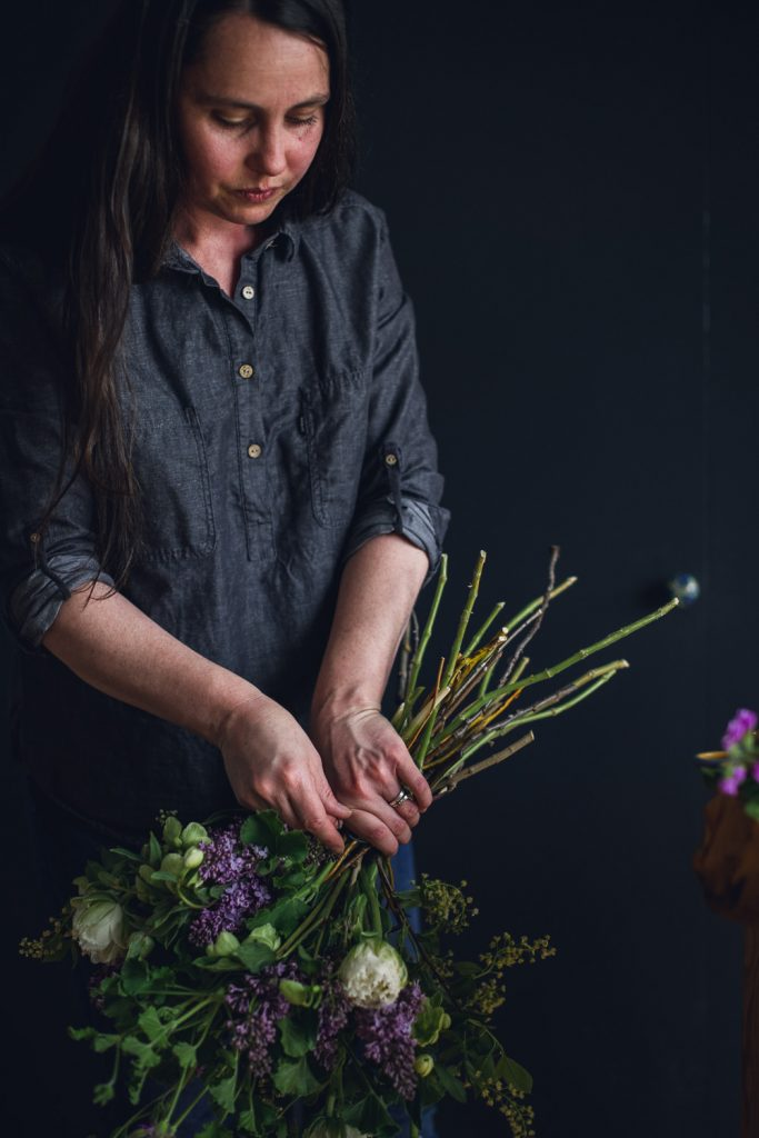 florist tying off a large spiral bouquet with colorado spring flowers