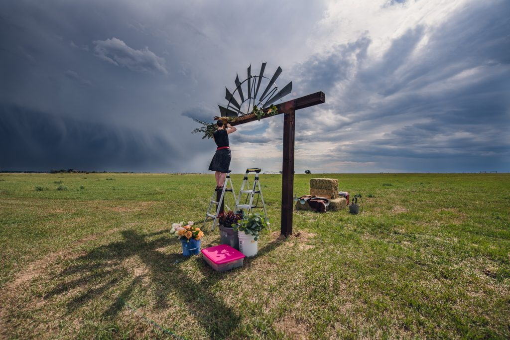 floral designer creating a flower arch for wedding in a colorado field with stormy skies