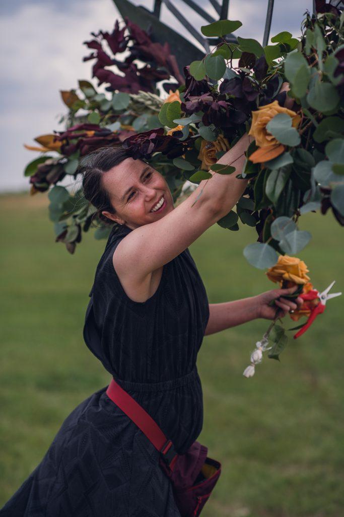 floral designer in a black dress creating a floral arch for wedding