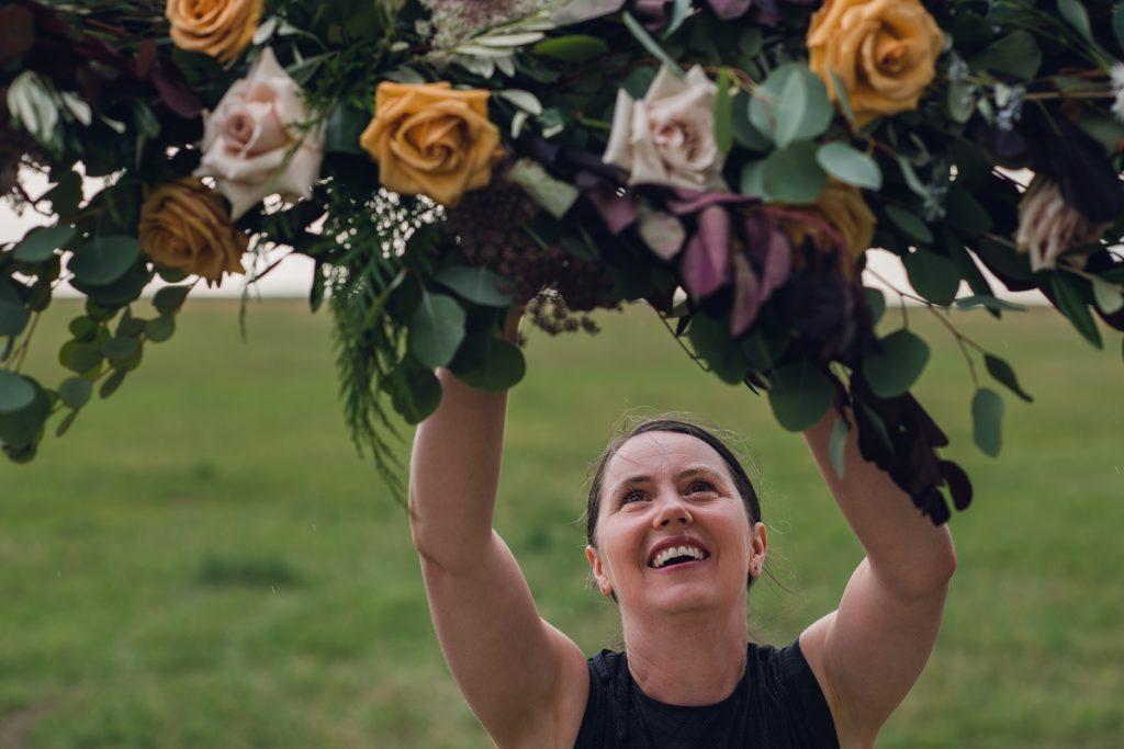 woman assembling a floral wedding arch