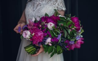 bride holding a vibrant pageant style bouquet of magenta and purple flowers