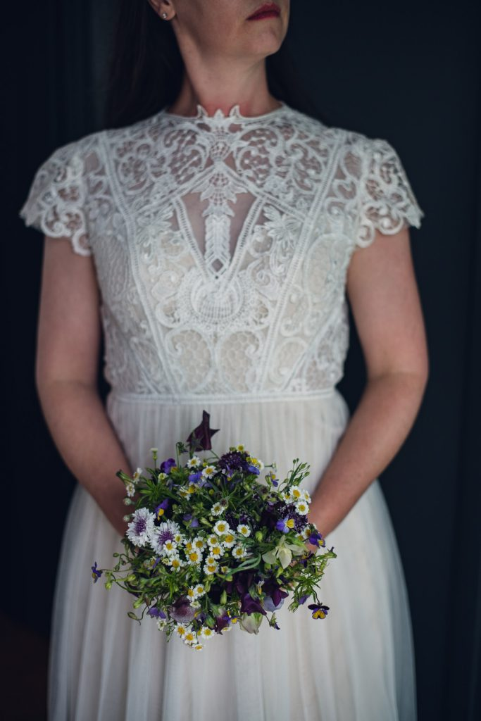 bride holding a small purple garden style bouquet