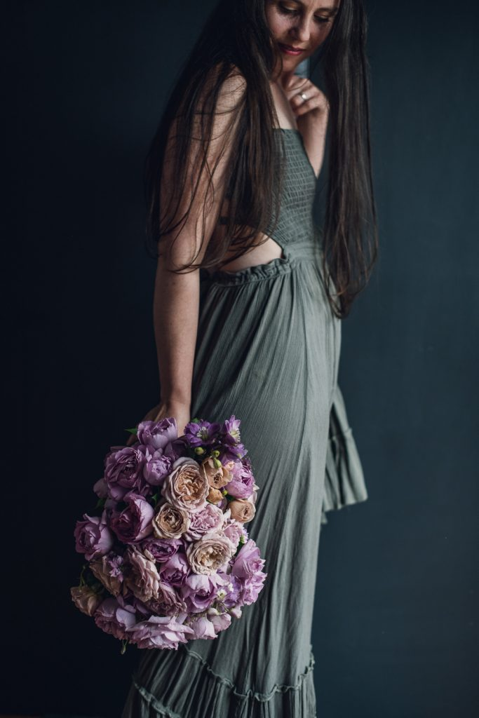 women in grey dress holding a dusty pink rose bouquet at her hip