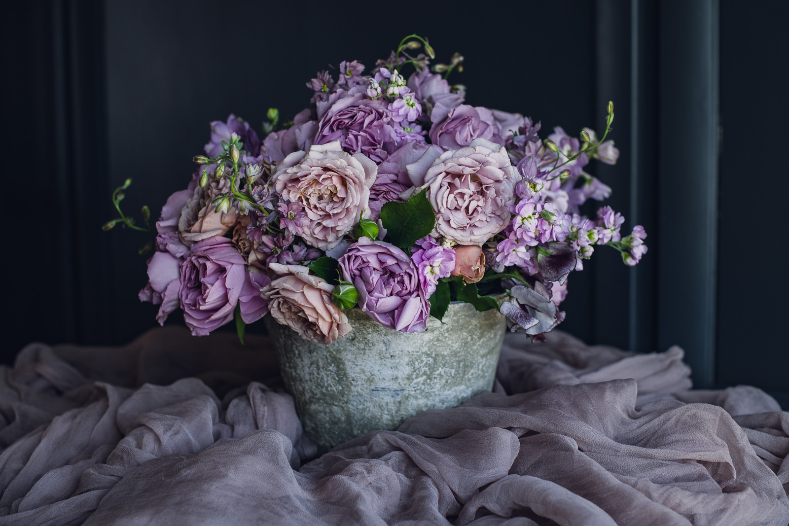 pink, purple and blush centerpiece in a grey ceramic container in a pile of fig color silk
