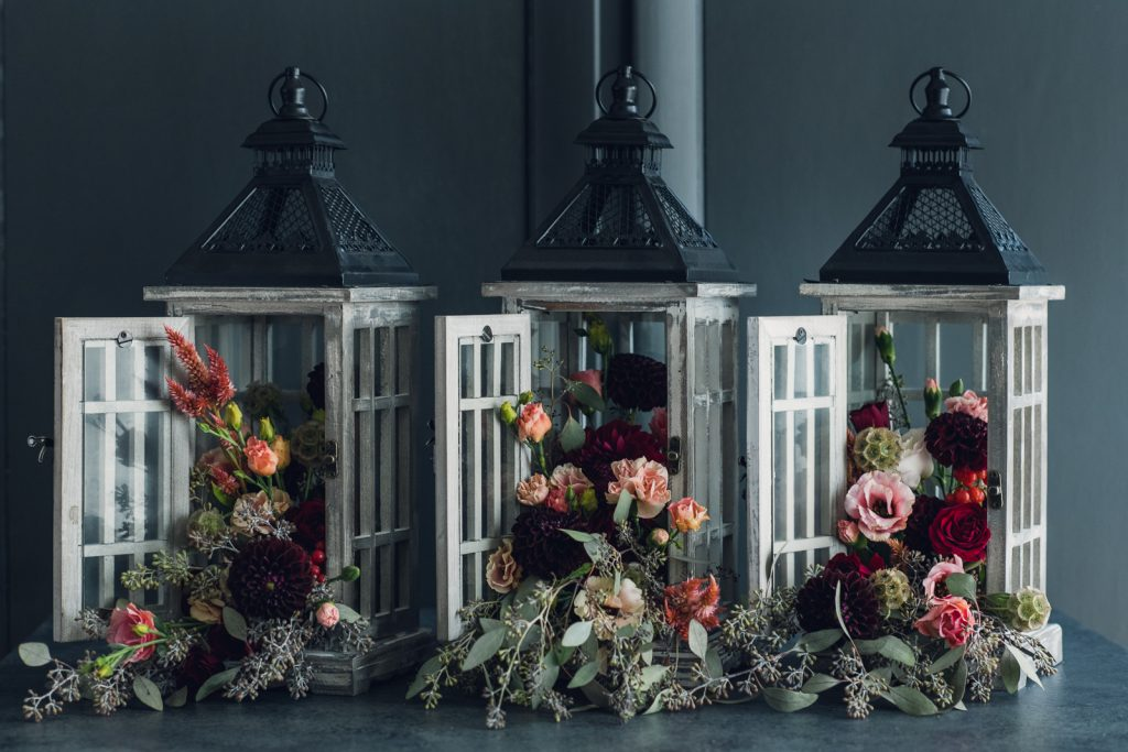 wood lanterns with flowers spilling out for wedding centerpieces