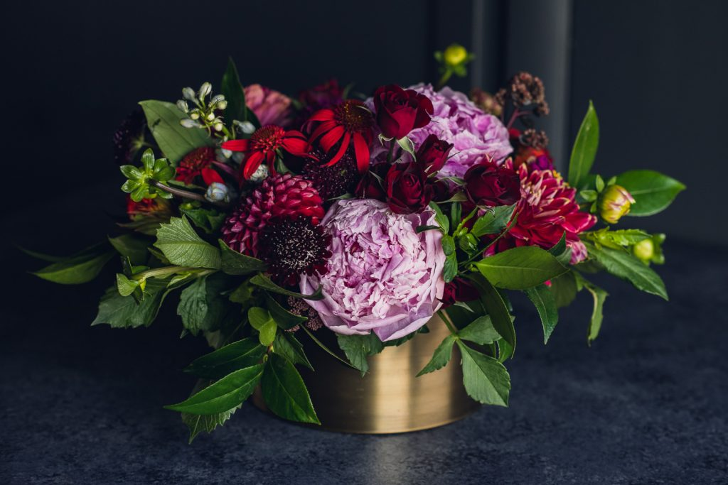 red and pink centerpiece in a gold container