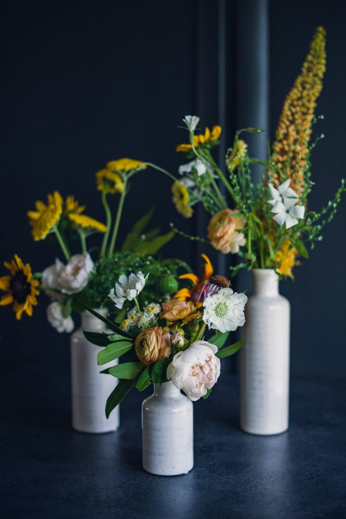 trio of white milk vases with yellow, green and pink flowers