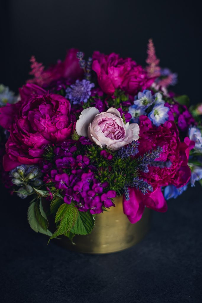vibrant magenta jewel tone flowers in a gold centerpiece container