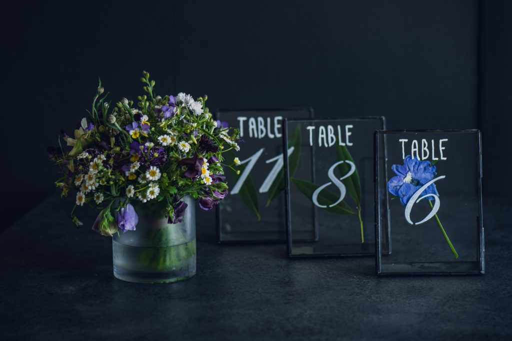 a small blue and purple centerpiece with glass table numbers for a wedding
